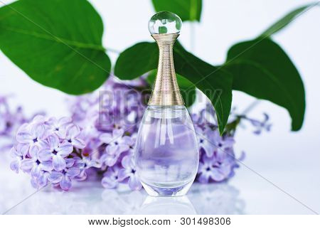 Perfume And Lilac Flowers On Gray Background