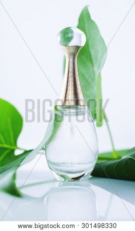Perfume With Green Leaves On White Background