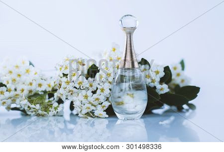 Female Perfume With White Flowers On Light Background