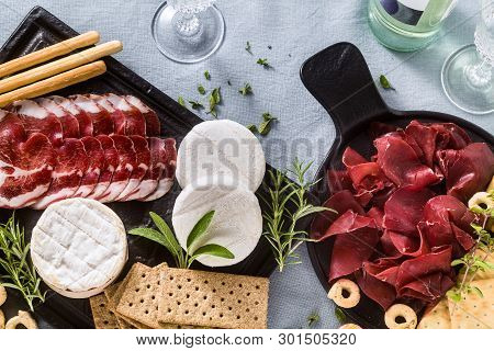 Italian Bresaola Served Sliced On A Tray On A Table With White Wine, Crackers, Grissini And Taralli