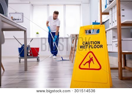 Male Janitor With Mop Cleaning Modern Office Floor