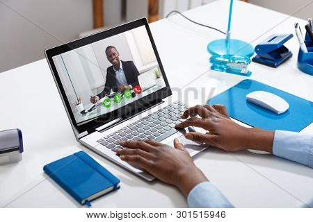 Businessperson's Videoconferencing With Male Colleague On Laptop