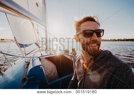 A Handsome Bearded Man In Sunglasses On A Boat On A River Or Lake. Beautiful Happy Guy Swimming In A