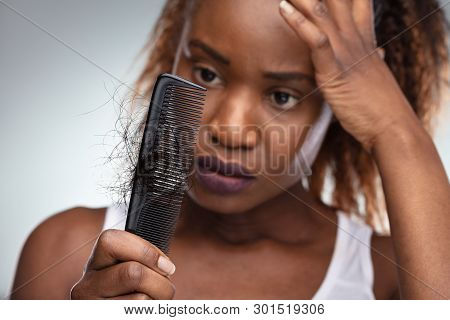 Close-up Of African Shocked Woman Suffering From Hair Loss Problem