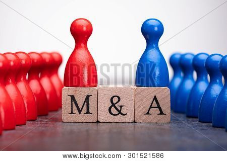 Close-up Of Red And Blue Pieces On Wooden Blocks With Mergers And Acquisitions Text