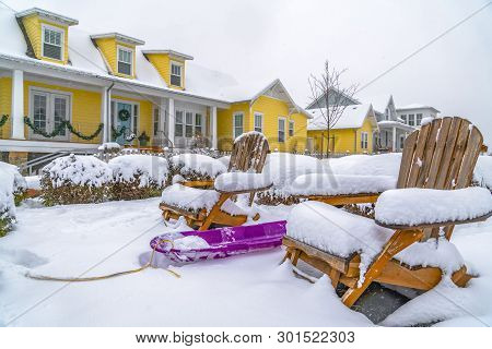 Winter In Daybreak With View Of A Purple Sled In The Middle Of Wooden Chairs