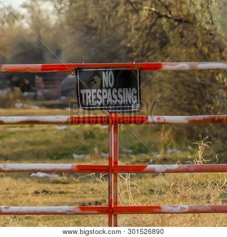 Clear Square No Trespassing Sign On The Gate Of A Private Property Viewed On A Sunny Day