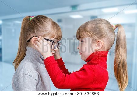 A Child Puts Glasses On His Twin Sister On A Blurred Background.
