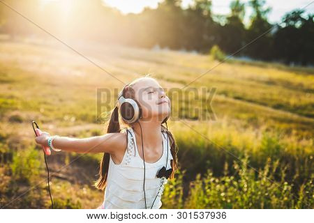 Fair Girl Listening Music With Headphones And Dancing, Lucky Child Listening Music And Spinning