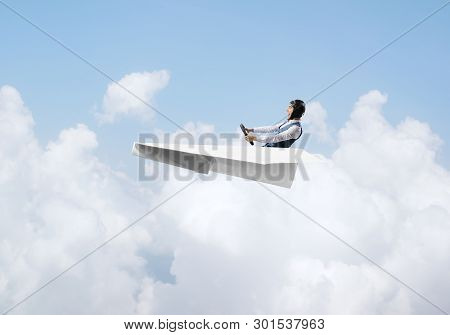 Aviator Having Fun In Aircraft. Pilot In Leather Helmet And Goggles Driving Paper Plane In Cloudy Bl