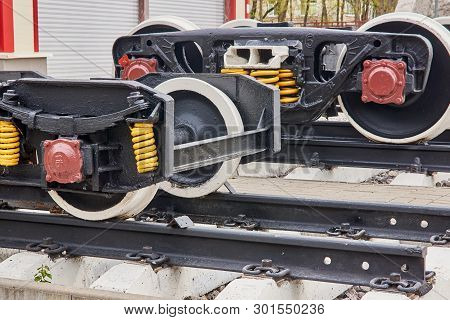 Railway wheels narrow gauge railway and ordinary railway. Freight cargo train or boxcar chassis, suspension and metal wheels stand on the rails, close-up poster