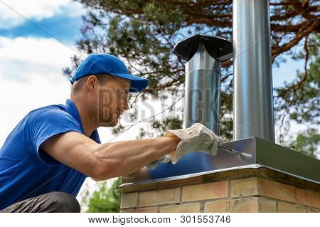 Worker On The Roof Installing Tin Cap On The Brick Chimney