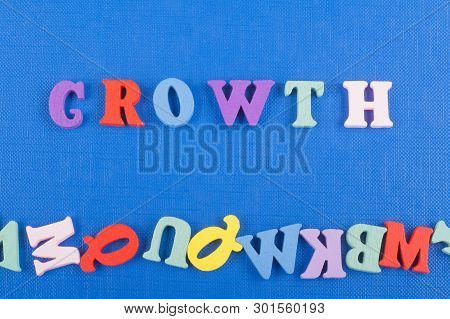 Growth Word On Blue Background Composed From Colorful Abc Alphabet Block Wooden Letters, Copy Space