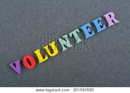Volunteer Word On Black Board Background Composed From Colorful Abc Alphabet Block Wooden Letters, C