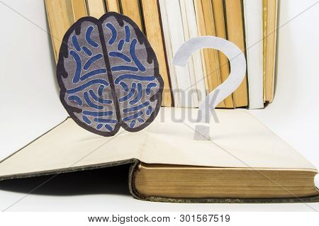 Paper Brain Silhouette And Question Mark Is Over Old Open Medical Book. Photo To Refer Issues And Qu