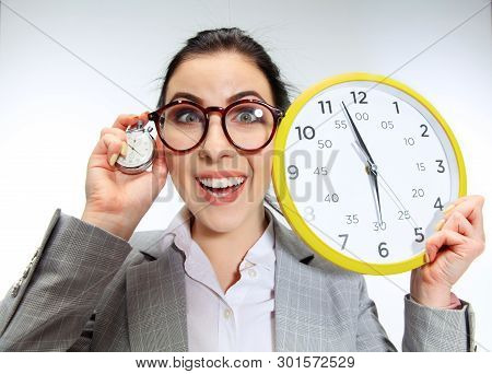 Young Woman Cant Wait To Go Home From The Nasty Office. Holding The Clock And Waiting Five Minutes B