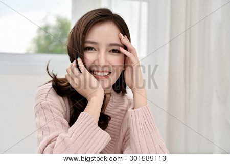 Relaxation Concept. The Beautiful Girl Is Smiling Happily Inside The Room. Beautiful Asian Girl Smil