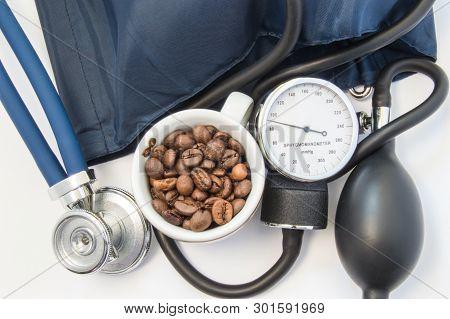 Caffeine And Blood Pressure. Small Mug With Coffee Beans, Symbolizing Caffeine Near Sphygmomanometer
