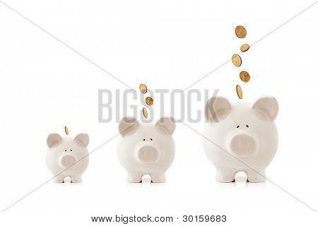 Steigerung in der Größe, mit Münzen fallen ihnen Sparschweine. wachsende Anlagekonzept.