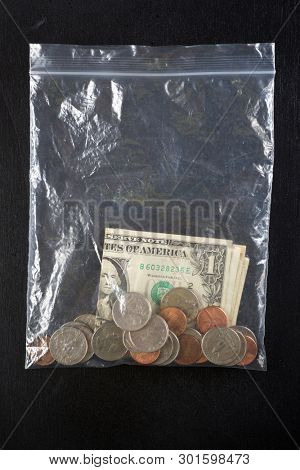 Dollar bills and coins in a plastic bag.