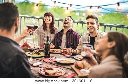 Young Friends Having Fun Drinking Red Wine At Balcony Penthouse Dinner Party - Happy People Eating B