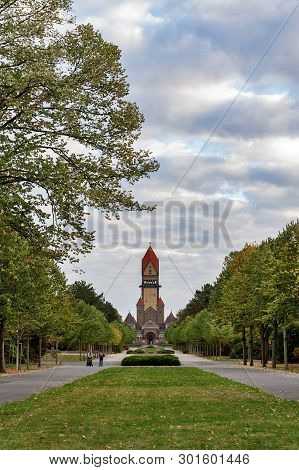 Leipzig, Germany - October 2018: Walkway In Beautiful Park Toward Chapel Complex, Bell Tower, Funera