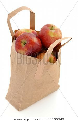 Apple fruit in a brown paper recycled carrier bag isolated over white background, red dessert variety.