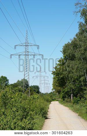 Overhead High-voltage Power Line Alongside Footpath Trough German Countryside