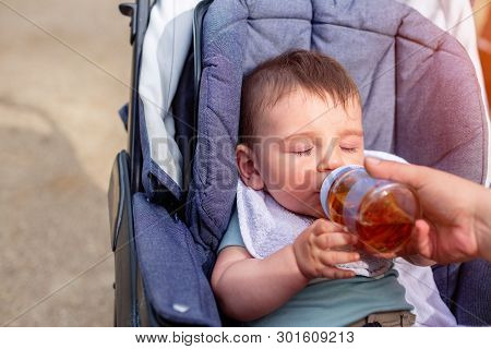 Cute Boy Drinks Juice From A Bottle While Sitting In A Baby Carriage On A Walk