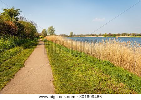 Narrow Footpath Parallel To The Water Of A Small Lake