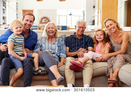 Portrait Of Multi-Generation Family Sitting On Sofa At Home Smiling At Camera