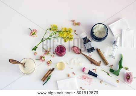 Top View Of A Bottle Of Essential Oil Next To The Twigs Of Plants And Fresh Flowers,  Fragrant Salt,