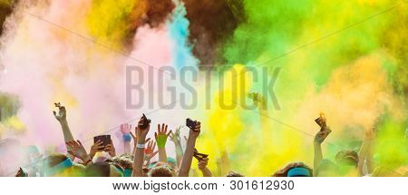 Crowd of people on color run throwing colored powder. Happy holi theme.