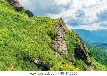 Summer Landscape In Carpathian Mountains. Huge Rocky Formation On The Edge Of A Grassy Slope. Ridge