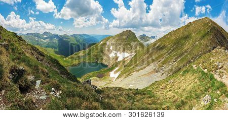 Panorama Of Fagaras Mountain In Summer. Glacier Lake Capra Between Hills. Beautiful Landscape With S