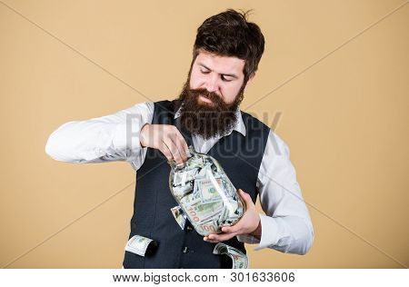 Making An Investment. Businessman Taking Cash Money Out Of Glass Jar For Investing Activities. Beard