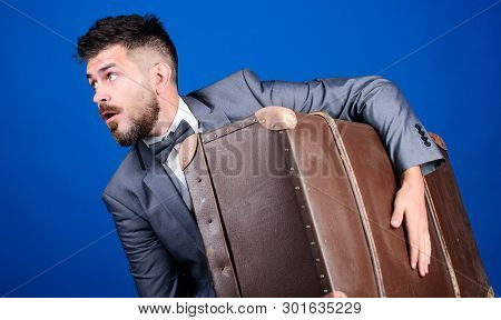 poster of business trip with retro suitcase. heavy bag. mature traveller. stylish esthete with vintage bag. bearded man in formal suit. surprised businessman in bow tie. Complementing his style with bag