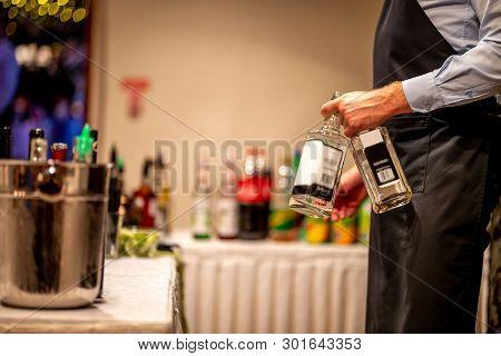Waiter Holds Two Whiskey Bottles In Hand. Waiter With Two Whiskey Bottles In Wedding Party. Ice Buck