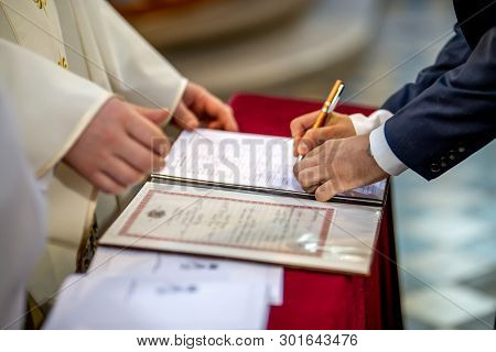 The Groom Signs Documents On Registration Of Marriage In The Presence Of The Pastor. Young Couple Si