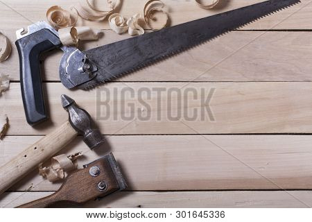 Construction tools on wooden table with sawdust. Joiner carpenter workplace top view. Copy space for text poster