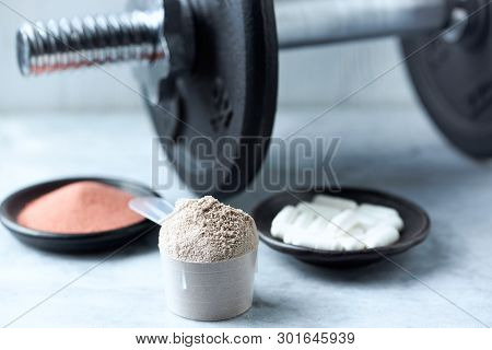 Scoop Of Whey Protein, Beta-alanine Capsules, Creatine Powder And A Dumbbell In Background. Sport Nu