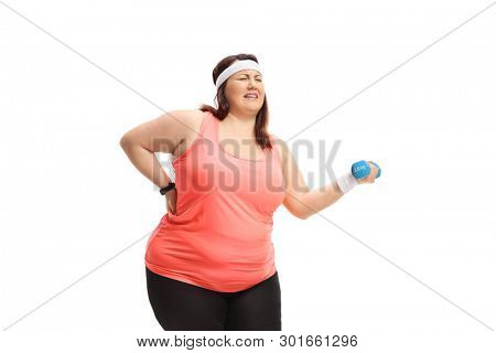 Overweight woman struggling to lift a small dumbbell isolated on white background