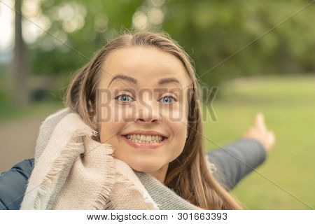 Young Woman Portrait. Excited Beautiful Woman Stands Sideways And Points With Finger In The Backgrou