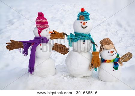 Cute Little Family Snowman Outdoor. Happy Family Of Snowman On A Background Snow-covered Fir Branche