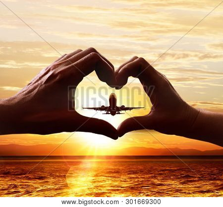 Hands of lovers in the form of heart, which against the background of the sky with the taking-off plane