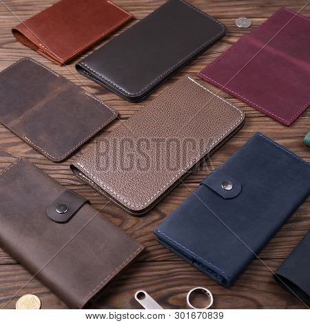 Light Brown Color Handmade Leather Porte-monnaie Surrounded By Other Leather Accessories On Wooden T