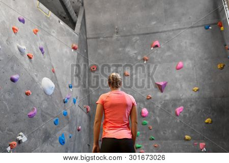 fitness, extreme sport, bouldering, people and healthy lifestyle concept - young woman at indoor climbing wall in gym from back