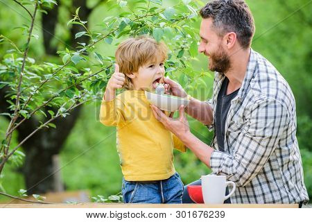 Family Enjoy Homemade Meal. Father Son Eat Food And Have Fun. Little Boy And Dad Eating. Nutrition F