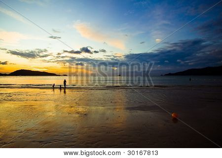 A Woman With Children On The Ocean Beach