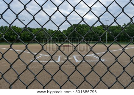 Baseball Field Through Chain Link Fence On Cloudy Day